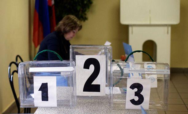 Vaalivirkailija valmistelemassa äänestyspistettä Moskovassa lauantaina.