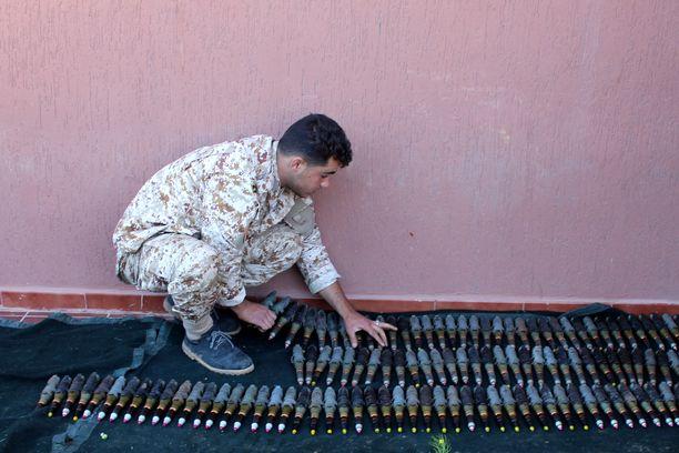 Sotilaallisen ryhmittymän jäsen valmistelee ammuksia ennen joukkojen etulinjaan suuntaamista. Mies taistelee YK:n tukeman Tripolin hallituksen puolesta.