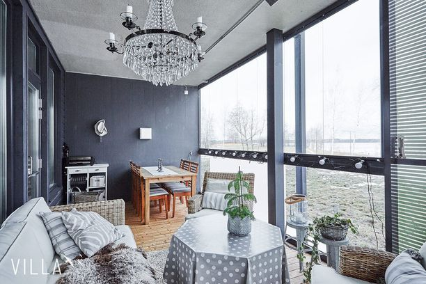 Tässä tilassa kattokruunu kynttilöineen tarjoaa hempeän tunnelmavalaistuksen. Jos lisävaloa tarvitaan, sitä tuo lasiseinään kytketty valosarja.