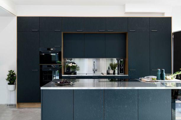 Mustat jykevät keittiöt ovat tulleet jäädäkseen. Metallisena hehkuva välitila tuo kontrastia mustille kaapeille.