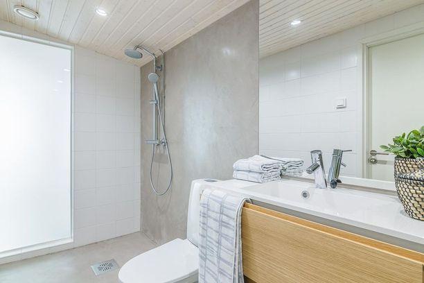 Erilaiset pinnat tekevät kylpyhuoneesta kiinnostavan. Tässä suihkuseinä ja lattia ovat mikrosementtiä. Olohuoneen ja kylpyhuoneen välissä on maitolasiseinämä, jonka läpi valo pääsee kylpyhuoneeseen.