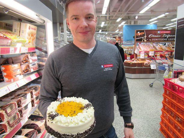 Citymarketin kauppias Marko Strand näyttää Tropical -kakkua kädessään ja lupaa panna perjantaina pannun kuumaksi kaupassaan.