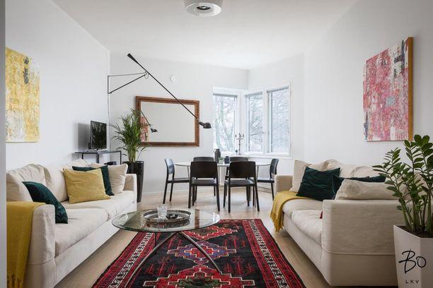 Vaaleat pinnat eivät ole este. Värikkäiden tekstiilien avulla saa luotua tyylikkään sisustuksen, jossa on persoonaa. Tässä kodissa keltainen, vihreä ja punainen luovat harmonisen kokonaisuuden. Värit toistuvat taiteessa, sohvatyynyissä ja matossa.