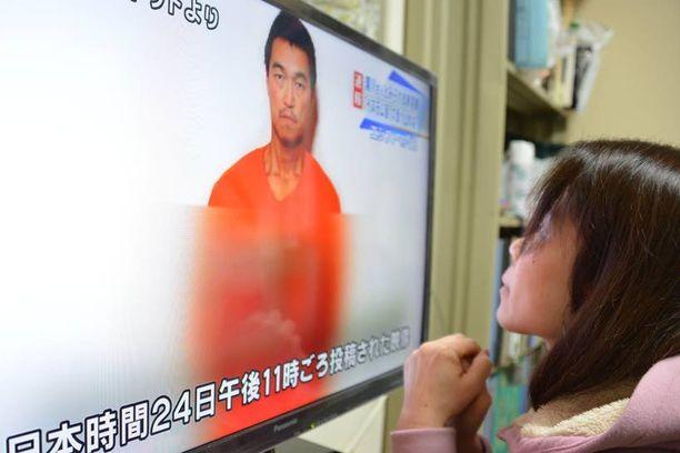Nainen katseli Tokiossa uutisia, joissa kerrottiin Kenji Goton vankeudesta Isisin kynsissä.