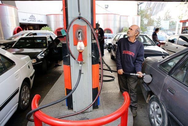 Mies tankkasi autoaan Iranin pääkaupunki Tehranissa perjantaina.
