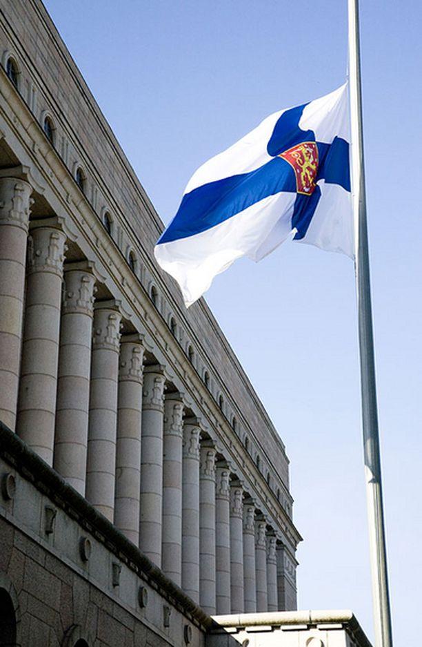 Suomen lippu puolitangossa eduskuntatalon edustalla.