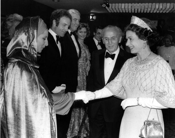 Huppulliseen viittaan pukeutunut näyttelijä Barbra Streisand ja kuningatar Elizabeth II.