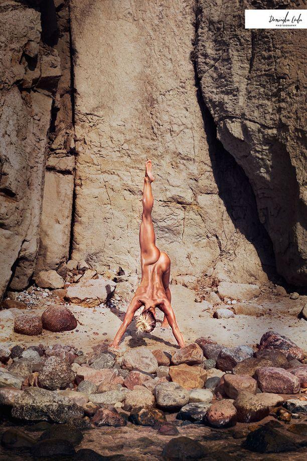 Bikini fitness -urheilija Katarzyna Dziurska taituroi pienen puron varrella sijaitsevalla rannalla.