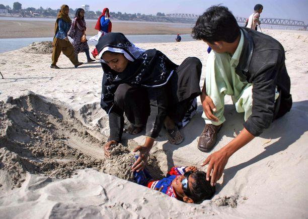 INDUS Halvaantuntta poikaa haudattiin hiekkaan Pakistanissa. Pojan lääkäri oli neuvonut hautaamaan pojan osittain hiekkaan pimennyksen ajaksi, koska uskoi sen paranatavan.