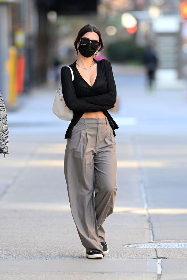 Emily Ratajkowski yhdistää väljät, suorat housut avonaiseen puseroon.