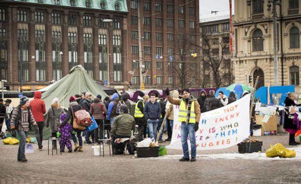 Turvapaikanhakijat osoittavat mieltä Helsingin Rautatientorilla.