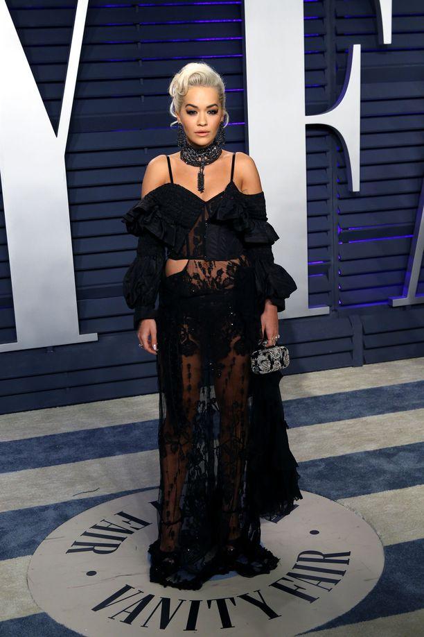 Rita Ora 2019 Vanity Fairin järjestämissä Orcar-gaalan juhlissa. Tämän kokonaisuuden hurmaavin kohta on muhkea kaulapanta, joka erottaa asun muista mustisa iltapuvuista. Vaikka asu on läpinäkyvä ja voisimme taivastella Oran vilautusta, kokonaisuus on erittäin harmoninen ja kaunis.