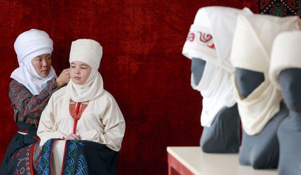 Kirgisiassa kunnioitetaan yhä enemmän perinteisiä arvoja, vaikka maassa pyritään muun muassa naisten ja miesten väliseen tasa-arvoon. Kuvassa naiselle sovitetaan peristeistä hääpäähinettä. Kuvituskuva.