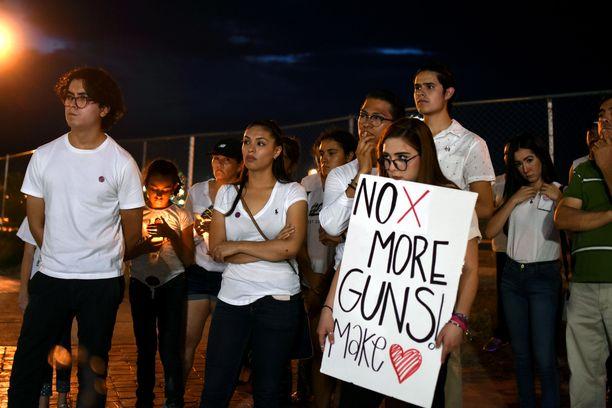 """Meksikolaiset pitivät rukoushetken Yhdysvaltojen ja Meksikon rajalla lauantaina illalla. """"Ei enää aseita"""", heidän kannattelemassaan kyltissä lukee."""