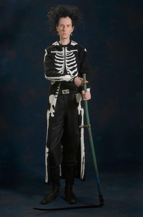 Kosmologi Syksy Räsänen on mallina kuvassa, jossa esitellään neuletakki Mort. Mort-takin henkeä kuvaillaan kirjassa muun muassa näin: Kuoleman näköinen mies asteli PRKL-klubille.