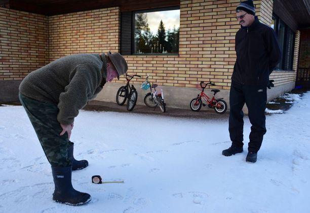 Suurpetoyhdyshenkilö Seppo Lehtonen (vas.) kävi mittaamassa Mauri Arposen pihalla olleet sudenjäljet todeten ne täysikasvuisten eläinten tekemiksi. Matkaa lasten polkupyöriin ja taloon on vain muutama metri.
