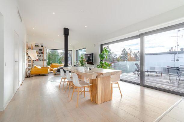 Olohuoneen ja keittiön välissä on tilaa isolle ruokapöydälle. Huonekorkeus, isot ikkunat ja vaaleat pinnat tekevät tilasta avaran ja valoisan.