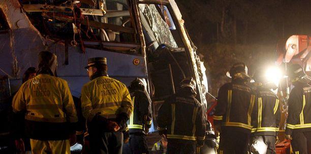 Espanjalaiset palomiehet tutkivat bussiturman tuhoja.