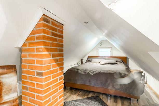Yläkerran makuuhuone on pieni, mutta sinne on saatu mahdutettua iso parisänky ja jopa pieni sivupöytä. Kodissa on hyödynnetty vaaleita pintoja, jotka tuovat pieneen tilaan lisää avaruutta.