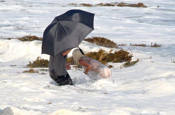 Avustaja pelastaa Lady Gagan vellovasta merestä.