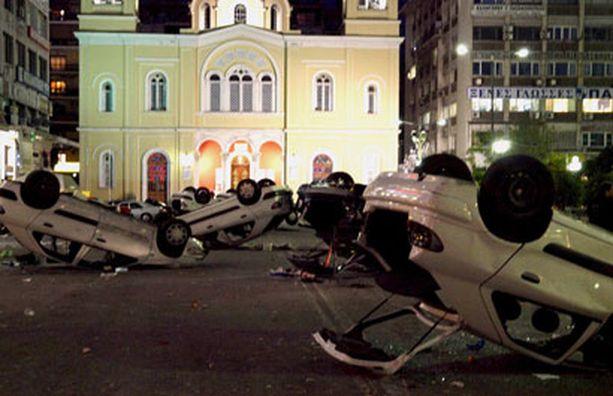 Mellakoitsijat käänsivät autoja poliisiaseman edessä.
