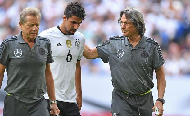 Saksan maajoukkueen lääkäri Hans-Wilhelm Mueller-Wohlfahrt ja fysioterapuetti Klaus Eder saattelevat Italia-ottelun ensimmäisellä puoliajalla loukkaantunutta Sami Khediraa pois kentältä.