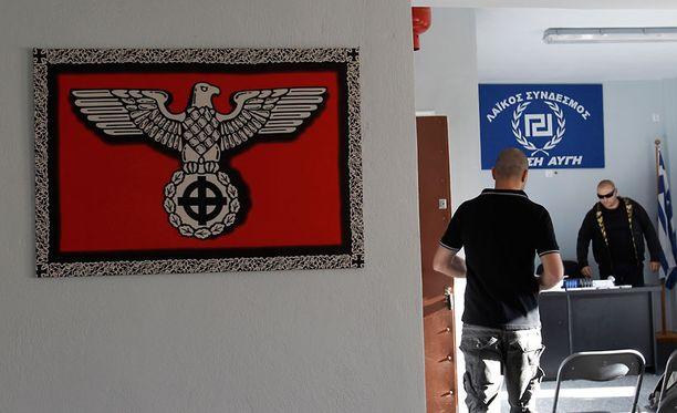 Kultaisen aamunkoiton ehdokas Giorgios Germanis (oik.) puolueen toimistossa Artemisissa. Seinää koristaa natsityylinen juliste, jossa hakaristi on korvattu kelttiläisellä ristillä.