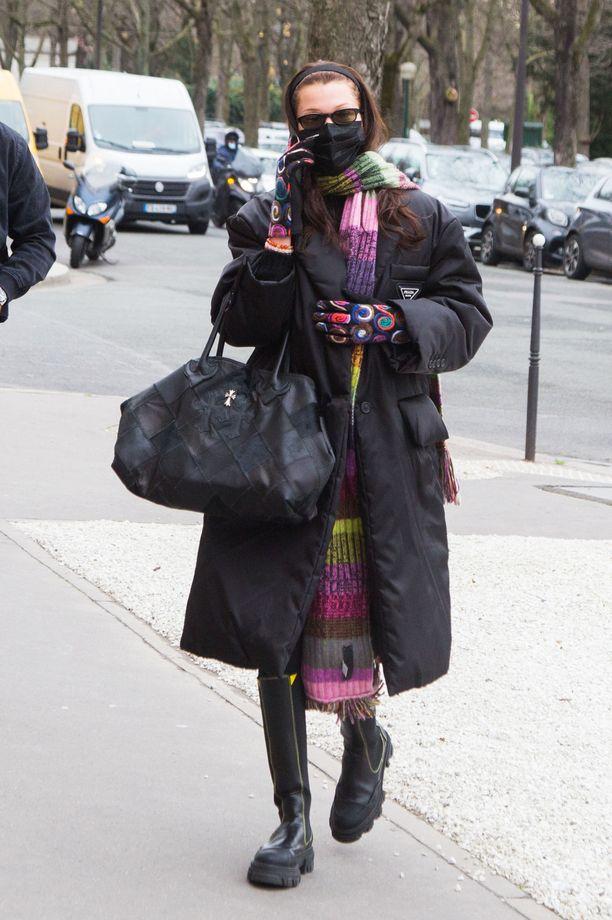 Bella Hadid yhdistää Pradan takkiin ja Gannin buutseihin tuntemattoman liikkeen värikkäät käsineet.