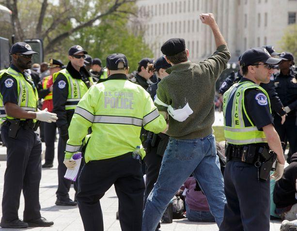 Poliisi vei mielenosoittajaa pois paikalta.