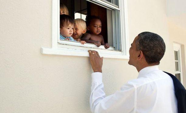 Obama tervehtii kuvassa lapsia. Tviitin lainaus on Nelson Mandelalta.