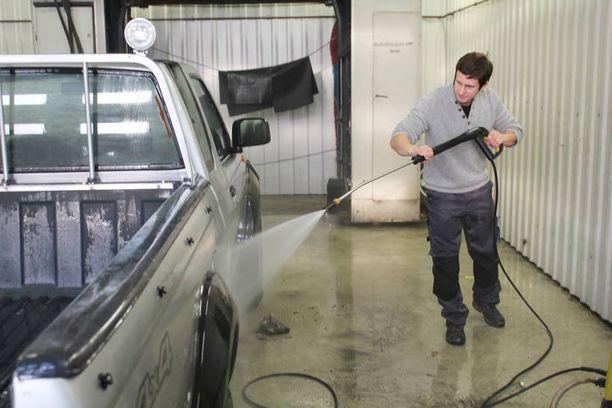 Talvipakkasilla Panu Hiltula antaa autojen sulaa hallissa ennen pesua.