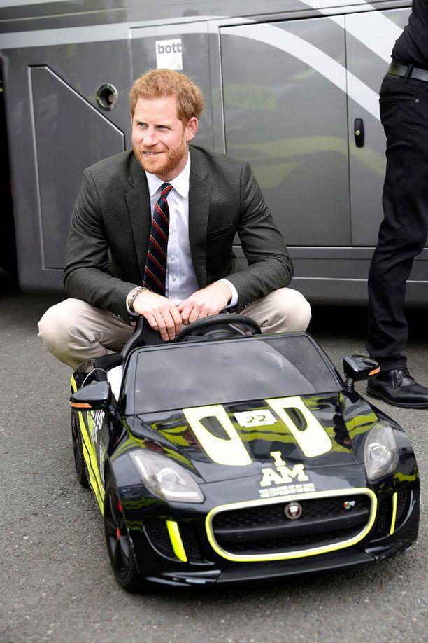 Prinssi poseerasi kuvaajille ikään kuin pikkuautoon ahtautuneena.