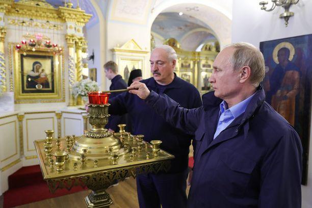 Venäjän presidentti Vladimir Putin ja Valko-Venäjän presidentti Aleksandr Lukashenko sytyttävät kynttilän vieraillessaan Konevitsan luostarissa Laatokalla 17.7.2019.