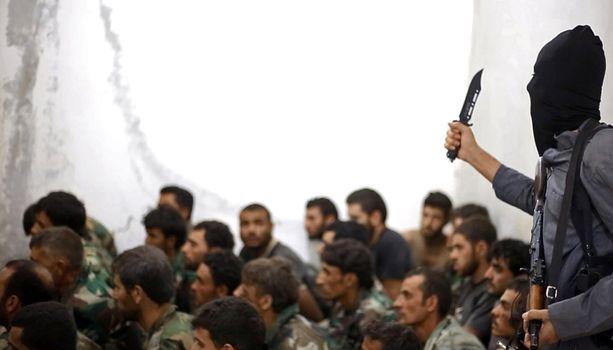 Arezu annettiin Isis-miliantin orjaksi. Kuvassa Isis-taistelija syyrialaisten sotavankien kanssa Raqqan kaupungissa.
