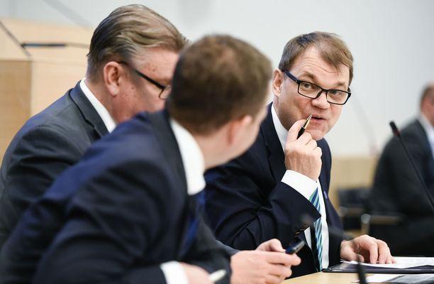 Keskustan Juha Sipilän (oik.) johtama hallitus yrittää pusertaa sote-uudistusta väkisin maaliin.