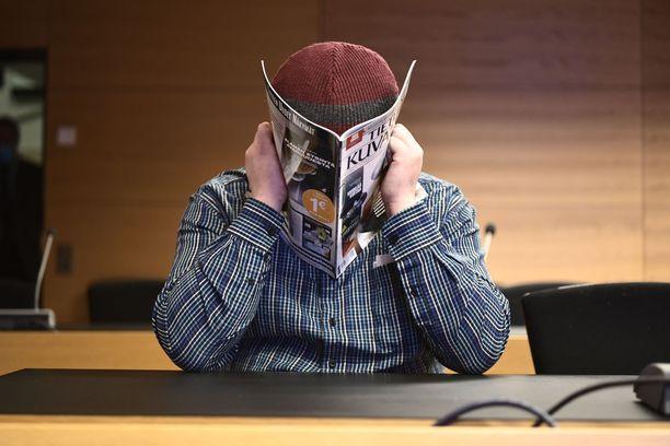 Syytetty peitti kasvonsa aikakauslehdellä.