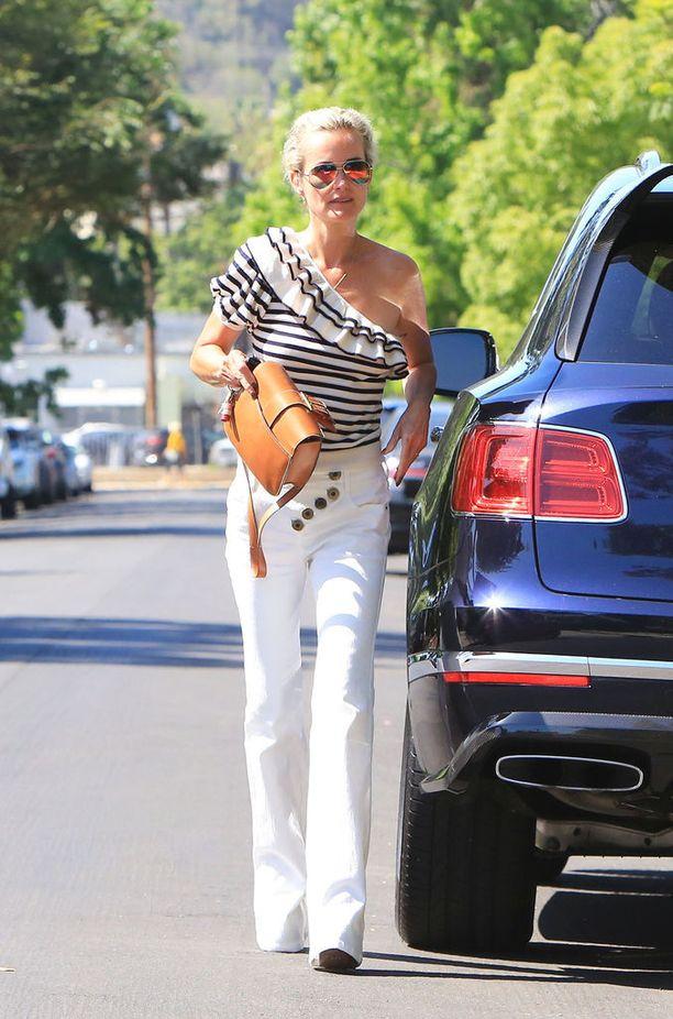 Malli Laeticia Hallyday yhdistää leveälahkeiset valkoiset farkut yksihihaiseen raitapaitaan, joilla syntyy näyttävä kesätyyli.