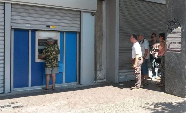 Ihmiset jonottivat Karaiskakin aukiolla Metaxourgion metroasemalla Ateenassa useille pankkiautomaateille maanantaiaamuna.