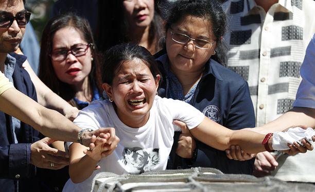 Kuolleena pakastimesta löydetyn naisen sisar Demafelisen arkun äärellä Manilan lentokentällä.