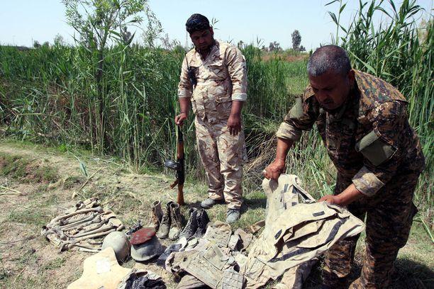 Irakilaissotilaat tutkivat epäillystä joukkohaudasta löytyneitä jäänteitä ja sotilasvarusteita Tikritissä vuonna 2015.