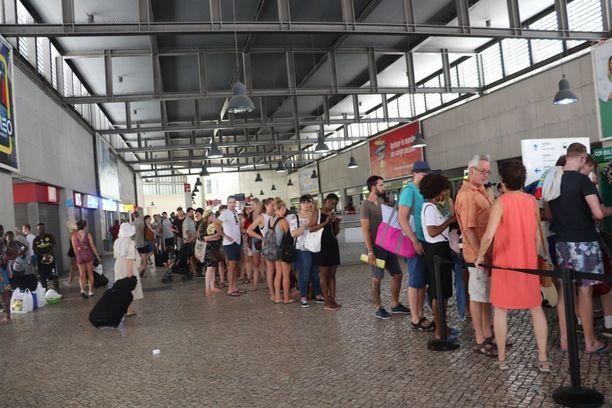 Ihmiset hellevaatteissaan jonottivat Cascaisiin meneviin juniin, joka on Lissabonista 40 minuutin junamatkan päässä sijaitseva kunta aivan meren äärellä.