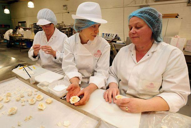 Kuuluisa kakkumaakari Fiona Cairns (kesk.) valmistelee hääkakkujen koristeita yhdessä kollegoidensa kanssa.