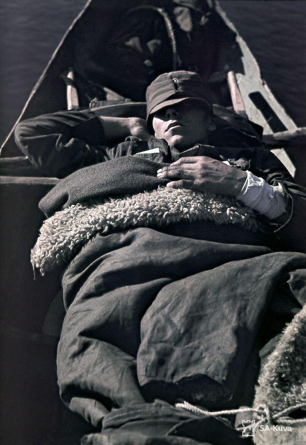Haavoittunutta sotilasta kuljetettiin jokiveneessä Petsamossa Luttojoella heinäkuussa vuonna 1942.