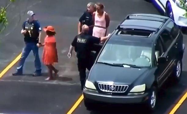 Äiti ja tytär löytyivät piilottelemassa perheen citymaasturissa parkkipaikalta. Poliisi johdattelee punamekkoisen tyttären pois.