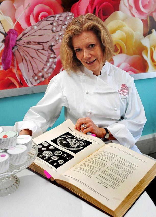 Hedelmäkakku saa perinteisen koristelun. Fiona Cairns poseeraa kuningatar Victorian aikaiset reseptikirjan kanssa.