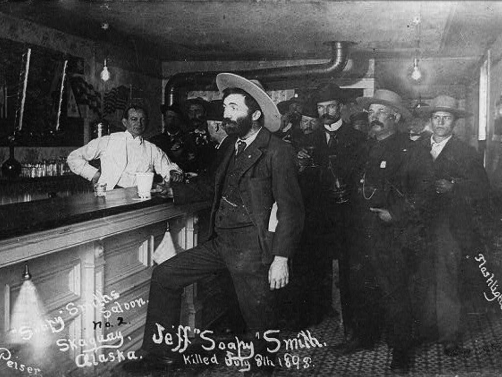 """Villin Lännen saluunat levisivät Alaskaan asti. """"Soapy"""" Smith, Klondiken-reitillä olleen Skagwayn kuuluisa huijari rentoutumassa omassa kapakassaan. Hän kuoli ammuskelussa 1898."""