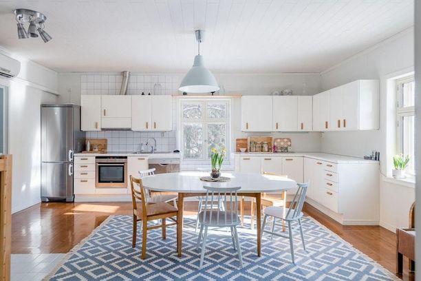 Vaikka lattia on ruskea, jatkuu keittiökaappien valkoisuus raikkaassa matossa. Matto tasapainottaa tilaa loistavasti.