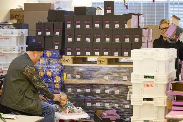 Ruoka-apua kolmen sukupolven voimin. Heikki Hursti leikittää 10 kuukauden ikäistä Zaraa, ja Sini Hursti purkaa ruoka-avustuksia.
