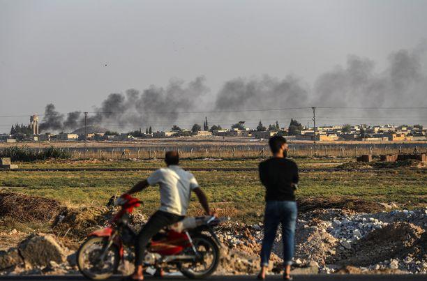 Ihmiset katselivat sunnuntaina Turkin puolelta rajaa, miten savu nousi Pohjois-Syyriasta. Turkki aloitti hyökkäyksensä keskiviikkona.