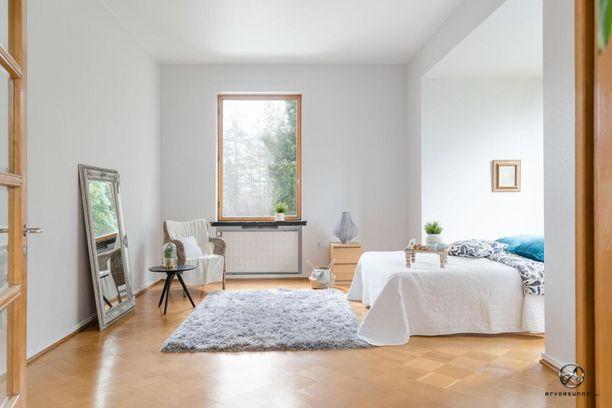 Korkeat ikkunat ja vaaleat seinät tekevät valoisuutta makuuhuoneeseen.